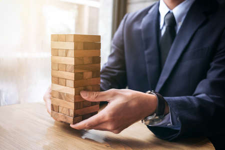 Foto de Alternative risk concept, plan and strategy in business, Young intelligent businessman raise the wood game, hands of executive sustain wood block on the tower, Collaborative management. - Imagen libre de derechos