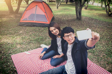 happy couple camping on the nature, taking a selfie shot of smiling with smartphone, camping, travel, tourism, hiking and people concept.