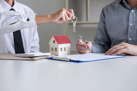 Photo pour Real estate Sales manager giving keys to customer after signing rental lease contract of sale purchase agreement, concerning mortgage loan offer for and house insurance. - image libre de droit
