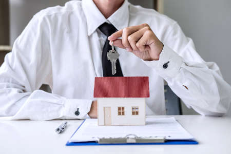 Foto de Real estate agent Sales manager holding filing keys to customer after signing rental lease contract of sale purchase agreement, concerning mortgage loan offer for and house insurance. - Imagen libre de derechos