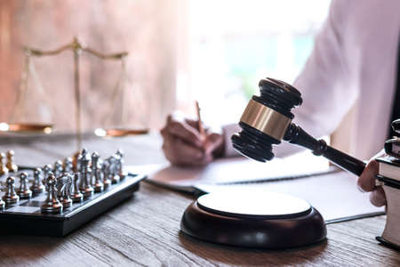 Photo pour Legal law, advice and justice concept, Professional male lawyers working on courtroom sitting at the table and signing papers with gavel and Scales of justice. - image libre de droit