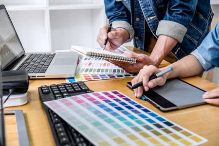 Foto de Young creative team having a meeting in creative office, Architectural drawing with work tools and accessories, Color swatch samples chart for selection coloring. - Imagen libre de derechos