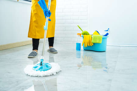 Photo pour Wife housekeeping and cleaning concept, Happy young woman in blue rubber gloves wiping dust using mop while cleaning on floor at home. - image libre de droit