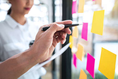 Photo pour Young creative team professional using notes in glass wall to writing strategy business plan to development grow to success. - image libre de droit