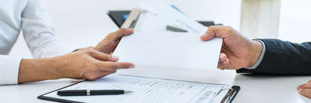 Hand of employer filing final remuneration after employee to write a document letter of resignation, resign concept.