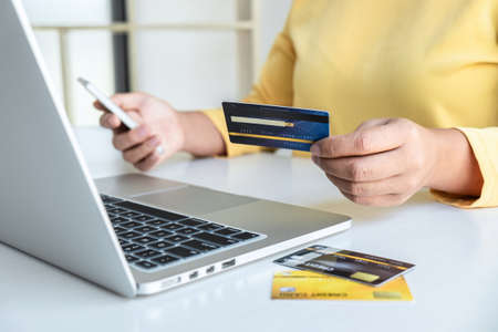 Woman using credit card and smartphone register security code payments online shopping and customer service network connection market, using technology on laptop, Internet Online shopping concept.