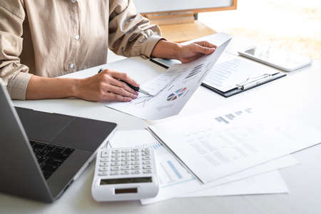Foto de Professional at work, business woman working and analyzing on laptop with calculate statistics of financial document data graph for new project of business strategy and market growth at workplace. - Imagen libre de derechos