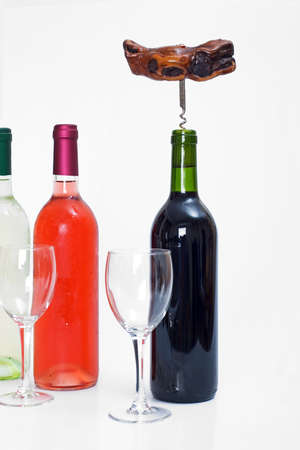 Bottles of red, white and rose wine with glasses and a corkscrew in the red bottle with a white isolated background