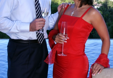 Smartly dressed couple chatting over Champage at a dinner party next to a swimming pool