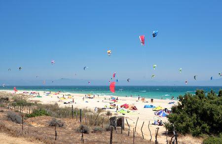 Beautiful white Tarifa beach in Spain packed with kitesurfers and sunbathers