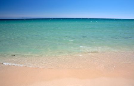 Gentle, calm lapping waves on sunny, sandy Tarifa beach in southern Spain