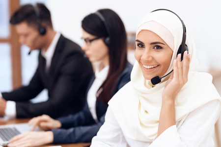 Photo pour An Arab woman works in a call center. She's an operator. Her colleagues work nearby. - image libre de droit