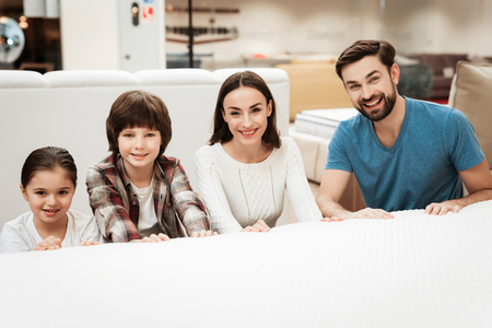 Young happy family sitting behind bed in orthopedic mattress store. Testing softness of mattress. Choosing mattress in store
