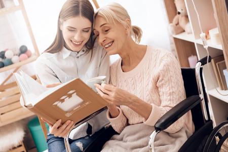 Foto de Girl is caring for elderly woman in wheelchair at home. They are looking at photos in photo album. - Imagen libre de derechos