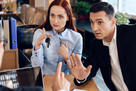 Red-haired woman is holding on finger keys sitting next to adult man in lawyer's office. Concept of property section under divorce. Adult couple is divorced.