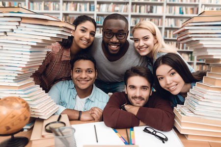 Foto de Six ethnic students, mixed race, indian, asian, african american and white sitting at table surrounded with books at library. - Imagen libre de derechos