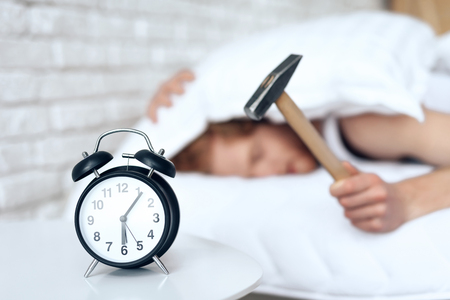 Photo pour Young red haired man hammers alarm clock. Lack of sleep. Morning awakening. Waking up. - image libre de droit