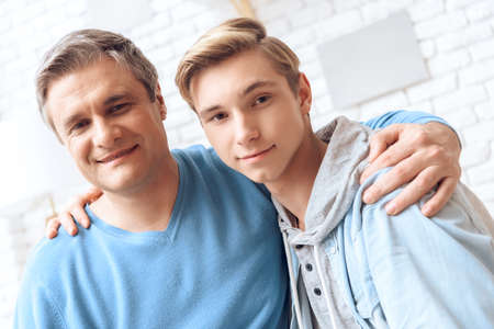 Photo pour Dad and son hug each other and look at the camera. - image libre de droit