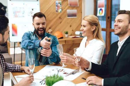 Photo pour Bearded man opens champagne with colleagues. - image libre de droit