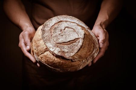Photo pour Baker man holding a beautiful round bread - image libre de droit