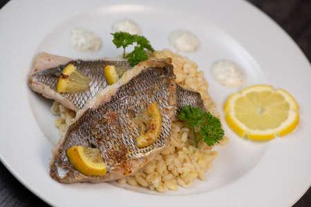 Photo pour Lemon-spiked sea bream fillet, cooked wheat risotto - image libre de droit