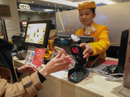Zhongshan,China-January 1, 2018:girl doing payment at a restaurant via mobile.Wechat or Alipay for payment and money transfering via mobile becomes very common and popular in China,fast and safe.