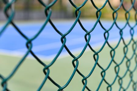 Photo for tennis court behind wire fence - Royalty Free Image