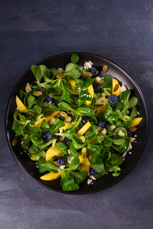 Mango, blueberries and cheese salad on black plate. View from above, top studio shot
