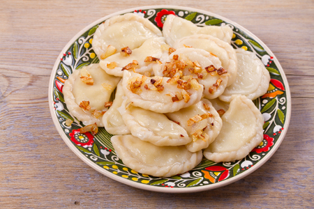 Dumplings, filled with potato and served with fried onion. Varenyky, vareniki, pierogi, pyrohy