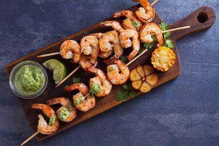 Foto de Cilantro lime grilled shrimps. Shrimps on skewers with garlic butter sauce. View from above, top studio shot - Imagen libre de derechos