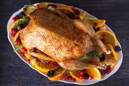 Photo pour Whole roasted duck with oranges, berries and herbs. View from above, top view - image libre de droit