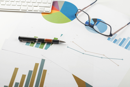 Background of workplace with economic graphics of various colors next to keyboard, ballpoint pen and glasses. Business concept.