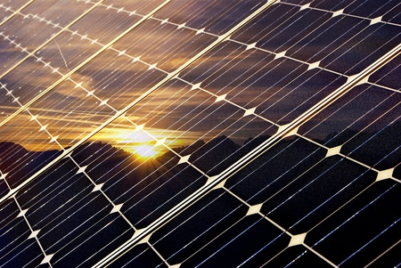 solar panel with mountains and setting sun, green economy