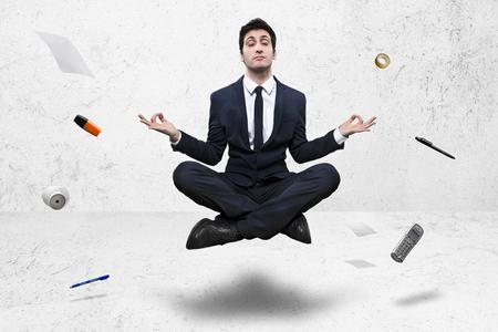 young businessman meditating in yoga lotus pose