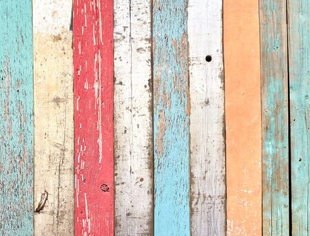 Foto de Texture of vintage wood boards with cracked paint of white, red, orange, yellow, cyan and blue color. Retro background with old wooden planks of different colors - Imagen libre de derechos