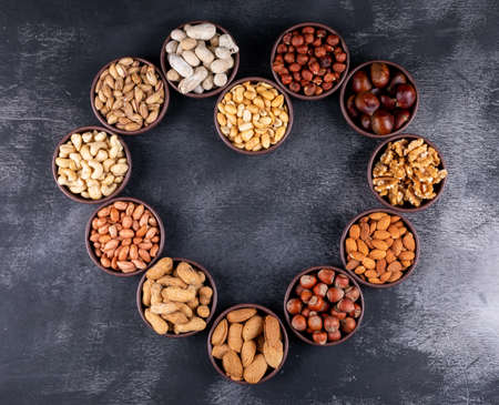 Photo pour Assorted nuts and dried fruits in a heart shaped mini different bowls with pecan, pistachios, almond, peanut, top view on a black stone background free space for your text - image libre de droit
