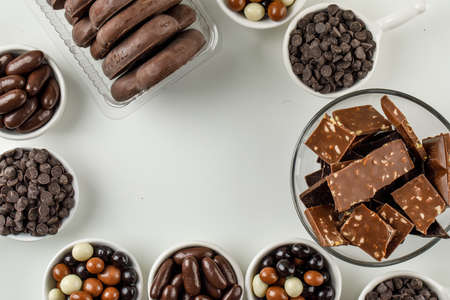 Photo pour Assorted chocolates in scoops and plates flat lay on a white background  - image libre de droit