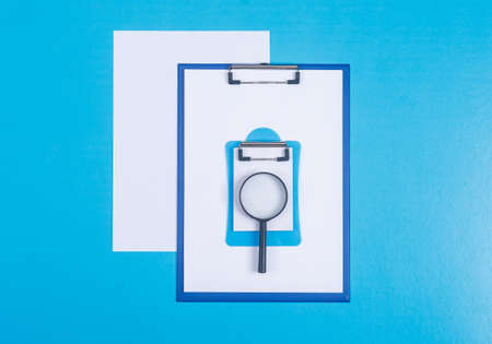 Conceptual of finance and accounting. with paper holder, notepad, paper, magnifier on cyan blue background top view. horizontal image