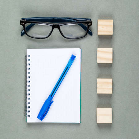 Photo for Conceptual of taking notes with notebook, pen, eyeglasses, wooden elements on gray background top view. - Royalty Free Image
