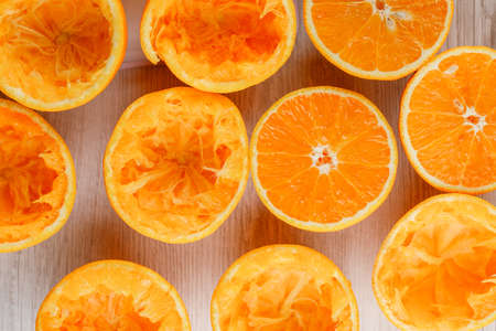 Photo pour Squeezed orange slices with fresh ones flat lay on a white wooden background - image libre de droit