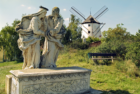 Austria, statue of saints with windmill in background
