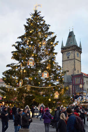 Prague, Czech Republic - December 2nd 2015: Unidentified people on Christmas market on old town square with Christmas tree and  tower of town hall
