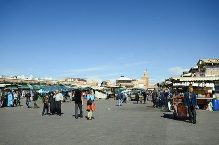 Marrakesh, Morocco - November 22nd 2014: Unidentified people and shops on Djemaa Elfna, tourist attraction and UNESCO World Heritage Site