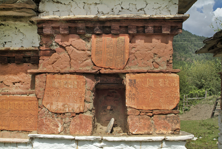 Bhutan, Mani wall with symbols in Paro valley