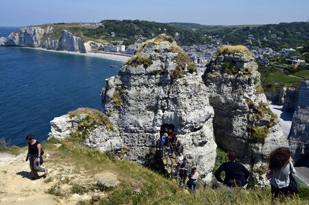 Etretat, France - June 2nd 2011: Unidentified tourists on the rock window with view to the beach of the little village on the English Channel