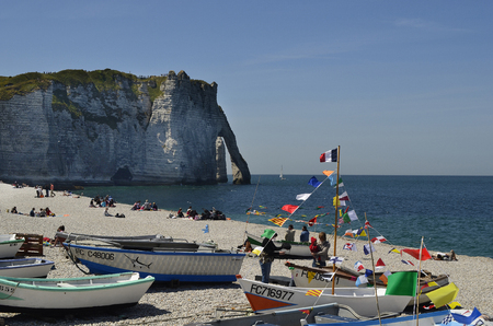Etretat, France - June 02, 2011: Unidentified people and boats on beach of the  sea ressort on Englsh Channel coast in Normandy
