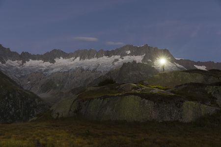 Alpinist with headlamp stands in the breathtaking mountain scenery of the Swiss Alps during the dawn of dawn