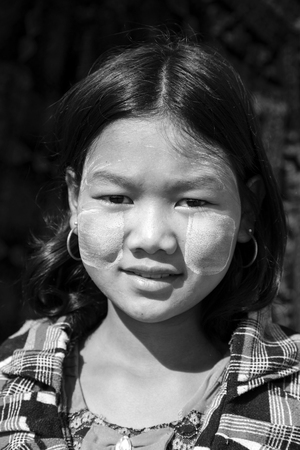Photo pour Bagan, Myanmar, December 27, 2017: Portrait of a young girl with tanaka paste on her face, - image libre de droit