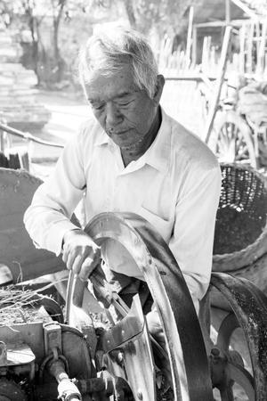Photo pour Bagan, Myanmar, December 27, 2017:  Old man grinds the knives of a harvesting machine - image libre de droit