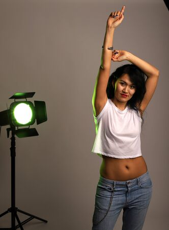 Foto de Studio photo of a girl with a yellow spotlight. Girl posing at camera with raised hand and protruding finger. A young girl in jeans and a short white T-shirt with an open belly button - Imagen libre de derechos